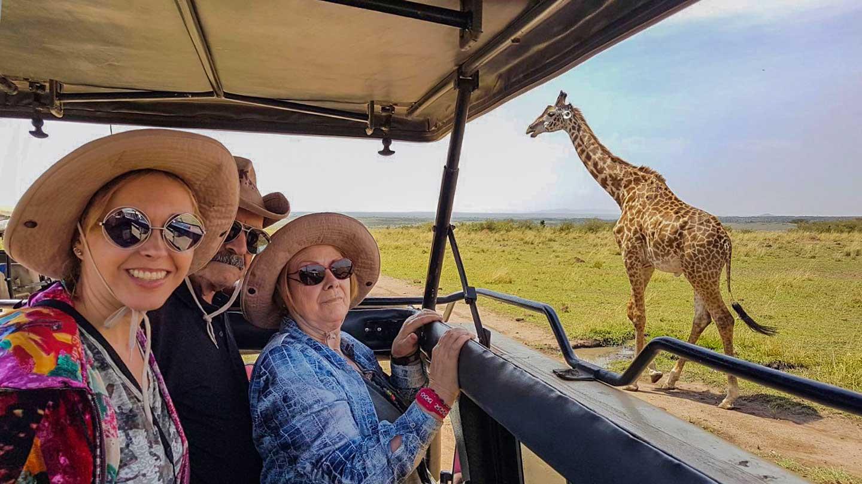 Familia durante Safari fotográfico en Kenia con una jirafa